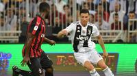 3. Cristiano Ronaldo mencoba melewati Christian Zapata pada laga Final Piala Super Italia yang berlangsung di stadion King Abdullah Sports City, Jeedah, Kamis (17/1). Juventus menang 1-0  atas AC Milan (AFP/Giuseppe Cacace)