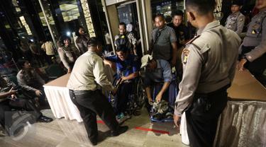Petugas kepolisian mengecek tamu undangan saat menghadiri Debat terbuka pertama Cagub-Cawagub DKI Jakarta, Jumat (13/1). Debat cagub-cawagub DKI Jakarta 2017 dihelat malam ini di sepuluh stasiun TV nasional. (Liputan6.com/Faizal Fanani)