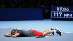 Petenis Jerman, Alexander Zverev tergeletak di lapangan setelah mengalahkan Novak Djokovic pada laga puncak ATP Finals 2018 di London, Senin (19/11). Zverev menjadi petenis termuda yang menjadi juara ATP Finals dalam satu dekade terakhir. (AP/Tim Ireland)