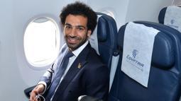 Bintang Mesir, Mohamed Salah, duduk di kursi pesawat saat tiba di Bandara Grozny, Chechnya, Minggu (10/6/2018). Pada Piala Dunia 2018, Mesir tergabung di Grup A bersama Rusia, Uruguay dan Arab Saudi. (AFP/Handout)