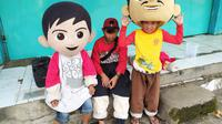 Para pengamen boneka yang masih duduk di bangku sekolah SD-SMP tersebut, nampak tengah beristirahat sambil menunggu lampu merah menyala di pertigaan lampu merah Toserta Asia, Garut, Jawa Barat. (Liputan6.com/Jayadi Supriadin)