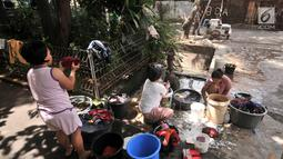 Warga mencuci pakaian di pinggir jalan kawasan Kramat Pulo, Senen, Jakarta, Kamis (27/12). Meski hanya menggunakan pompai air manual, warga Kramat Pulo mengaku nyaman mencuci di pinggir jalan karena gratis. (Merdeka.com/Iqbal S. Nugroho)