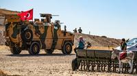 Warga lokal Suriah menyaksikan kendaraan militer Turki dan AS patroli gabungan di Desa al-Hashisha, Tal Abyad, Suriah, Minggu (8/9/2019). Pasukan Kurdi Suriah sendiri mulai menarik diri dari sepanjang perbatasan Turki pada akhir Agustus. (DELIL SOULEIMAN/AFP)