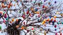 Seekor burung di antara 10.000 telur paskah warna-warni menghiasi pohon robinia di kota Saalfeld, Jerman, Jumat (30/3). Pohon Paskah, merupakan tradisi lain yang berumur berabad-abad dan dibuat dari pohon atau semak kecil yang masih hidup. (AP/Jens Meyer)