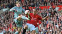 Striker Liverpool, Fernando Torres, berusaha melewati bek  Manchester United, Nemanja Vidic. Musim ini Torres dan Steven Gerrard tampil cukup memukau keduanya total mencetak 32 gol pada musim ini. (AFP/Andrew Yates)