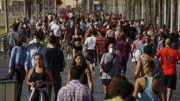 Warga Spanyol Sudah Beraktivitas di Luar Rumah: Warga berolahraga di trotoar pinggir laut di Barcelona, Spanyol, Sabtu (2/5/2020). Spanyol melonggarkan lockdown akibat pandemi COVID-19 mulai 2 Mei 2020. (AP Photo/Emilio Morenatti)
