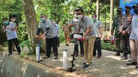 Wakil Wali Kota Depok Imam Budi Hartono saat membuat lubang biopori di pos pantau Sungai Ciliwung di Kelurahan Ratujaya, Kecamatan Cipayung, Kota Depok, Senin (22/3/2021). (Liputan6.com/Dicky Agung Prihanto)