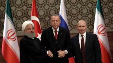 Presiden Turki Recep Tayyip Erdogan (tengah) bersama Presiden Rusia Vladimir Putin (kanan) dan Presiden Iran Hassan Rouhani (kiri) bergandengan tangan setelah konferensi pers bersama di Ankara, Turki, Rabu (4/4). (AP Photo/Burhan Ozbilici)