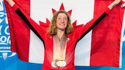 Ruck Taylor membentangkan bendera Kanada dengan delapan medali yang dikalunginya di Commonwealth Games 2018 di Gold Coast, Australia (10/4). Ruck mencatatkan rekor dari atlet lainnya dengan memenangkan medali terbanyak. (AP Photo/Ryan Remiorz)