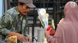 Pedagang dan pembeli bertransaksi bunga untuk hiasan Lebaran di Pasar Peterongan Semarang, Kamis (14/6). Sejumlah pedagang bunga mengaku meraup keuntungan yang cukup besar pada momen menjelang Lebaran kali ini. (Liputan6.com/Gholib)