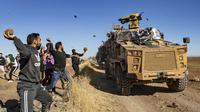 Sejumlah warga Kurdi melemparkan batu ke kendaraan militer Turki di dekat kota Al-Muabbadah, bagian timur laut Hassakah, Suriah (8/11/2019). Aksi dilakukan memprotes  terhadap serangan militer yang dilancarkan Turki. (AFP/Delil Souleiman)