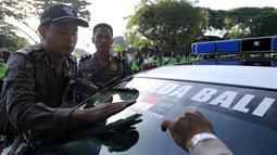 Polisi menempelkan stiker bendera Indonesia dan Arab Saudi selama persiapan menyambut kedatangan Raja Arab Saudi Salman bin Abdulaziz di Nusa Dua, Bali (2/3). Raja Salman akan berlibur di Bali tanggal 4 sampai 9 Maret. (AFP Photo / Sonny Tumbelaka)