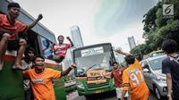 Suporter Persija bersorak saat menuju stadion Gelora Bung Karno, Jakarta, Minggu (9/12). Antusiasme ribuan suporter Persija bersiap mendukung tim kesayangannya bertanding melawan Mitra Kukar. (Liputan6.com/Faizal Fanani)