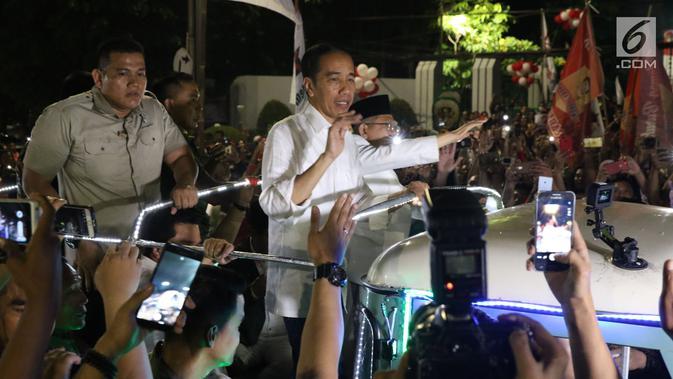 Calon Presiden RI Petahana, Joko Widodo bersama Cawapres Ma'ruf Amin menyapa pendukungnya saat berada di atas jeep menuju gedung KPU dari Tugu Proklamasi, Jakarta, Jumat (21/9). (Liputan6.com/Helmi Fithriansyah)