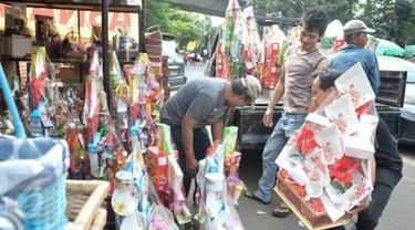 Pedagang menaikan parcel ke atas mobil di kawasan Pasar kembang, Cikini, Jakarta, Jumat (16/12). Jelang hari raya Natal, pedagang parcel di kawasan Cikini masih sepi pembeli. (Liputan6.com/Yoppy Renato)