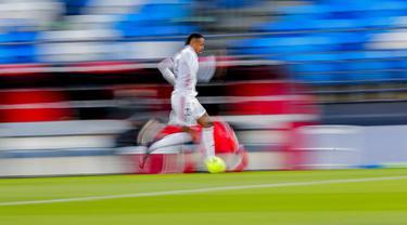 Pemain Real Madrid Eder Militao berlari dengan bola saat melawan Sevilla pada pertandingan La Liga Spanyol di Alfredo di Stefano Stadium, Madrid, Spanyol, Minggu (9/5/2021). (AP Photo/Manu Fernandez)