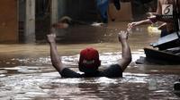 Warga melintasi banjir di Jalan Kebon Pala, Kampung Melayu, Jatinegara, Jakarta Timur, Rabu (7/2). Setelah sempat surut, banjir kembali merendam permukiman warga dengan ketinggian air mencapai sekitar 170 cm. (Liputan6.com/Arya Manggala)