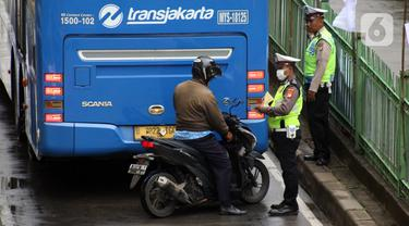 Petugas kepolisian lalu lintas merazia pengendara sepeda motor yang melintasi jalur bus Transjakarta di Jalan Sultan Agung, Manggarai, Jakarta, Kamis (6/2/2020). Meski melanggar, sebagian pengguna jalan secara sengaja masuk dan menggunakan jalur khusus bus tersebut. (Liputan6.com/Helmi Fithriansyah)