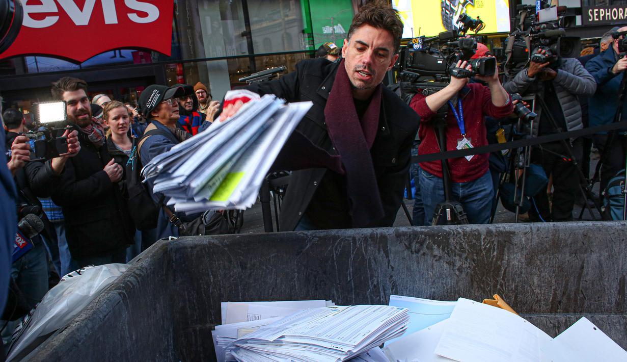 Seorang pria melempar kertas berisi kenangan menyulitkan ke tempat sampah selama kegiatan Good Riddance Day ke-13 tahunan di Times Square, New York, 28 Desember 2019. Kegiatan menjelang tahun baru tersebut menjadi tradisi untuk menghapus kenangan buruk selama satu tahun. (Kena Betancur / AFP)