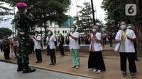 Tenaga kesehatan dan nonkesehatan bertepuk tangan selama 56 detik pada peringatan Hari Kesehatan Nasional ke-56 di RSD Wisma Atlet, Jakarta, Kamis (12/11/2020). Aksi tersebut sebagai bentuk penghargaan kepada tenaga kesehatan yang berjuang menghadapi pandemi COVID-19. (Liputan6.com/Herman Zakharia)
