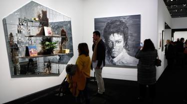 """Pengunjung melihat lukisan seniman AS Rashid Johnson """"The Whiz"""" (2012) dan """"In Memory of Michael Jackson"""" (2017) karya seniman China Yan Pei-Ming dalam pameran Michael Jackson: On The Wall di museum Grand Palais, Paris, Rabu (21/11). (AP/Francois Mori)"""