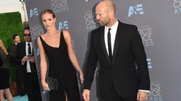 Rosie Huntington Whiteley bersama tunanganya Jason Statham saat tiba pada ajang Critics' Choice Awards ke-21 di Santa Monica, California, Minggu (17/1). Mereka dikabarkan bertunangan waktu berlibur bersama ke Thailand. (Jason Merritt/Getty Images/AFP)