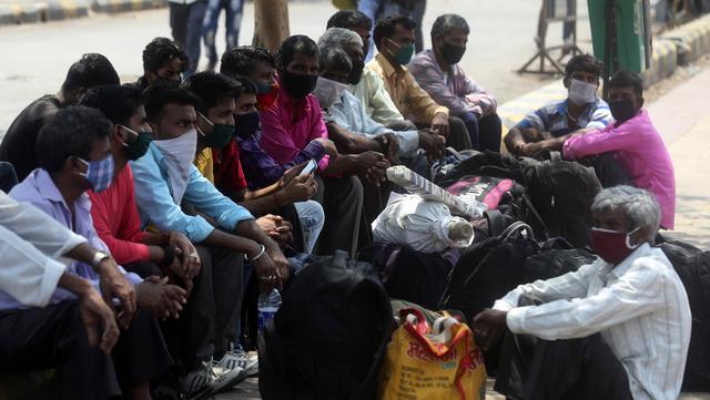 Pekerja migran dari negara bagian Bihar yang mengenakan masker wajah menunggu kereta di stasiun kereta Lokmanya Tilak di Mumbai, India, Rabu (7/4/2021). India mencapai puncak baru dengan 115.736 kasus COVID-19 dalam 24 jam. (AP Photo/Rafiq Maqbool)
