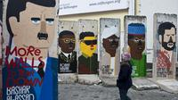 Seorang gadis melihat-lihat bekas Tembok Berlin yang digambari dengan karikatur para pemimpin dunia. Graffiti itu dilukis oleh artis Prancis Guillaume Kashima, dekat Checkpoint Charlie di Berlin, Jerman, 13 Januari 2013. (John MacDougall/AFP)