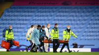 Petugas medis dalam APD lengkap membawa pemain Manchester City Eric Garcia yang cedera saat menghadapi Arsenal pada laga Premier League di Etihad Stadium, Manchester, Inggris, Rabu (17/6/2020). Manchester City menang dengan skor 3-0. (LAURENCE GRIFFITHS/POOL/AFP)