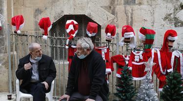 Orang-orang duduk di depan sejumlah kostum Sinterklas yang dipajang di dekat sebuah toko di Kota Tua Yerusalem (7/12/2020). (Xinhua/Muammar Awad)