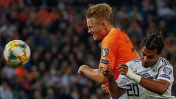 Bek Belanda, Matthijs De Ligt, duel udara dengan gelandang Jerman, Serge Gnabry, pada laga Kualifikasi Piala Dunia 2022 di Hamburg, Jumat (6/9). Jerman kalah 2-4 dari Belanda. (AFP/Odd Andersen)