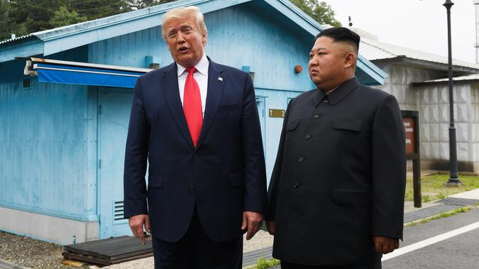 Presiden Amerika Serikat, Donald Trump bertemu dengan Pemimpin Korea Utara, Kim Jong-un di zona demiliterisasi Korea (DMZ), Desa Panmunjom pada Minggu (30/6/2019).  Ini adalah kali pertama seorang presiden AS menginjakkan kaki di negara tersebut. (AP Photo/Susan Walsh)