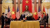 Presiden AS Donald Trump dan Presiden Vietnam Nguyen Phu Trong menyaksikan penandatanganan Ketua Bamboo Airways Trinh Van Quyet dan CEO Boeing Commercial Airplanes Kevin McAllister jelang KTT AS-Korut kedua di Hanoi (27/2). (AFP Photo/Luong Thai Linh)