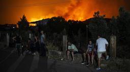 Sejumlah warga menunggu untuk dievakuasi dari desa Psachna selama kebakaran hutan di dekat desa Makrimalli di pulau Evia, timur laut Athena, Yunani (13/8/2019). Akibat kebakaran hutan ini perdana menteri Yunani membatalkan liburanya. (AFP Photo/Angelos Tzortzinis)