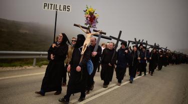 Jemaat katolik Ujue Virgin berbaris membawa salib saat melakukan ziarah dari Tafalla dan desa-desa lainnya ke kota kecil Ujue, Spanyol Utara (29/4). Mereka berjalan sekitar 25 km (16 mil) dari desa mereka menuju Ujue. (AP/Alvaro Barrientos)