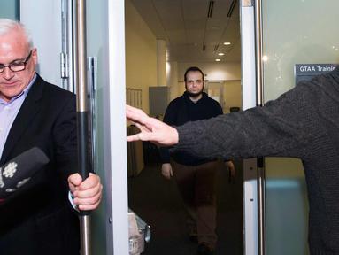 Joshua Boyle (tengah) tiba di bandara Toronto, Kanada (13/10). Pria asal Kanada ini disandera bersama istrinya Caitlin Coleman, dan ketiga anaknya oleh pasukan taliban di Afghanistan. (Nathan Denette / The Canadian Press via AP)
