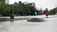Warga melintas dekat sebuah mobil yang terendam banjir setelah Badai Harvey menghantam kota Houston, Texas, Minggu (27/8). Banjir bandang yang dibawa Badai Harvey telah membuat Houston, kota terbesar keempat di AS, semakin terisolasi (AP/David J. Phillip)