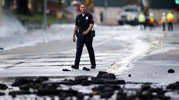 Seorang anggota kepolisian berjalan melintasi pecahan aspal akibat rusaknya pipa utama saluran air bawah tanah di sekitar Sunset Boulevard di bagian Westwood Los Angeles, (29/7/2014). (REUTERS/Danny Moloshok)