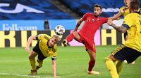 Bek timnas Swedia, Filip Helander (kiri) berebut bola dengan gelandang timnas Portugal, Bruno Fernandes pada laga UEFA Nations League A Group 3 di Friends Arena, Stockholm, Selasa (8/9/2020). Portugal kalahkan Swedia 2-0 lewat sepasang gol yang dicetak Cristiano Ronaldo. (Jonathan NACKSTRAND/AFP)