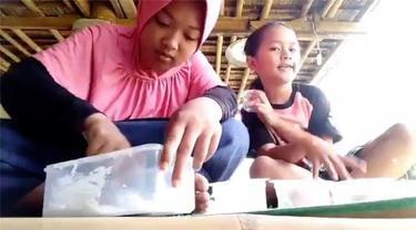 Dua anak perempuan menunjukkan cara membuat slime. Di tengah proses pembuatan salah satu dari mereka tercebur ke kolam.