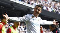 Bintang Real Madrid, Cristiano Ronaldo, merayakan gol yang dicetaknya ke gawang Atletico Madrid pada laga La Liga Spanyol di Stadion Santiago Bernabeu, Madrid, Minggu (8/4/2018). Kedua klub bermain imbang 1-1. (AFP/Gabriel Bouys)