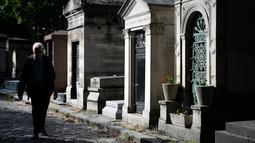Seorang pria berjalan melewati kuburan di pemakaman Pere Lachaise di Paris (22/7/2019). Pemakaman ini paling banyak didatangi wisatawan di dunia. Artis dan banyak tokoh terkenal dimakamkan di sini. (AFP Photo/Philippe Lopez)