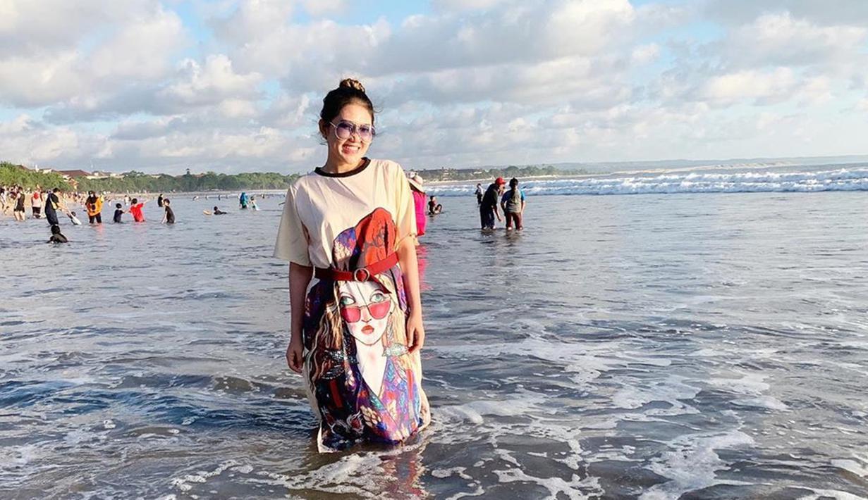 Via Vallen selalu tampil modis di berbagai kesempatan. Misalnya saat berlibur di Bali bersama keluarga. Tak terkecuali gayanya saat bermain air di pantai. Via mengenakan baju lajuran dengan ikat pinggang yang terlihat serasi. Ia juga tampak cantik dengan rambut digelung. (Liputan6.com/IG/viavallen)