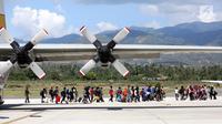 Warga Palu bersiap masuk ke pesawat Hercules TNI AU tujuan Makasar-Malang di Bandara Mutiara Sis Al-Jufri Palu, Sabtu (6/10). Pesawat Hercules yang membawa warga Palu terbang tiga kali dalam sehari. (Liputan6.com/Fery Pradolo)