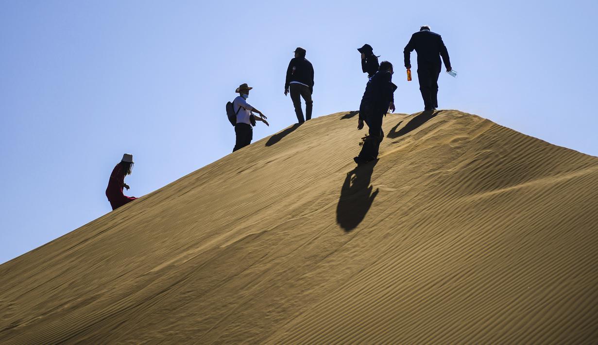 Para wisatawan mengunjungi kawasan wisata Gurun Kum Tag di Wilayah Shanshan, Kota Turpan, Daerah Otonom Uighur Xinjiang, China barat laut (22/9/2020). Gurun tersebut saat ini mencatat peningkatan arus wisatawan. (Xinhua/Wang Fei)