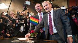 Pasangan gay, Bode Mende (kanan) dan Karl Kreile (kiri) menuliskan akta nikah mereka saat upacara pernikahannya di balai kota Schoeneberg di Berlin, Jerman (1/10). (AFP Photo/Odd Andersen)