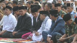 Presiden Joko Widodo sebelum salat id Hari Raya Idul Fitri 1 Syawal 1439 H di di Lapangan Astrid, Kebun Raya Bogor, Jumat (15/6). Jokowi hadir pukul 06.35 WIB mengenakan koko putih dengan jas hitam serta peci hitam dan sarung. (Merdeka.com/Arie Basuki)