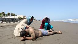 Seorang wanita Iran meletakkan pasir di punggung ayahnya di pantai di kota Laut Kaspia, Izadshahr, Mazandaran (8/7/2019). Dalam sejarah, laut ini disebut Samudra Hyrcania. Nama tua lainnya untuk Laut Kaspia termasuk Laut Mazandaran, Laut Khazar dan Laut Khvalissian. (AFP Photo/Atta Kenare)