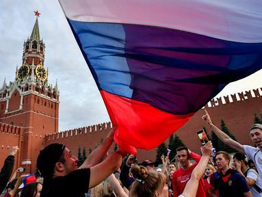 Suporter Rusia berpesta merayakan keberhasilan negaranya mengalahkan Spanyol pada laga 16 besar Piala Dunia di Moskow, Minggu (1/7/2018). Rusia untuk pertama kalinya lolos ke babak perempatfinal. (AFP/Yuri Kadobnov)
