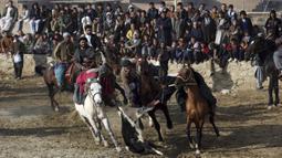 Penunggang kuda berebut kambing pada pertandingan persahabatan buzkashi di pinggiran Kabul, Afghanistan, Jumat (27/12/2019). Olahraga ini sempat dilarang selama pemerintahan Taliban. (AP Photo/Rahmat Gul)